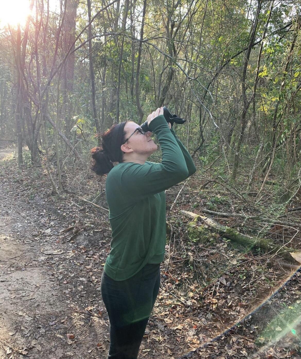 Amanda Hull peering at a Bald Eagle.